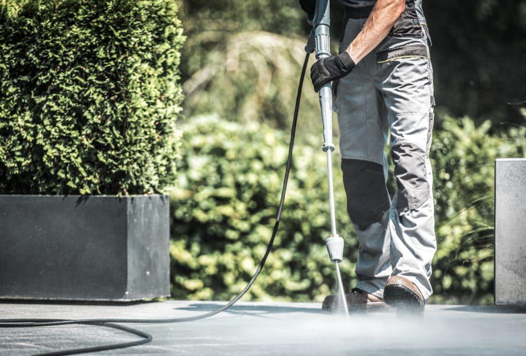 Ein Mann reinigt die Terrasse mit einem Hochdruckreiniger