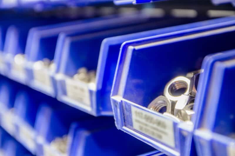 Schrauben in dunkelblauen Behältern
