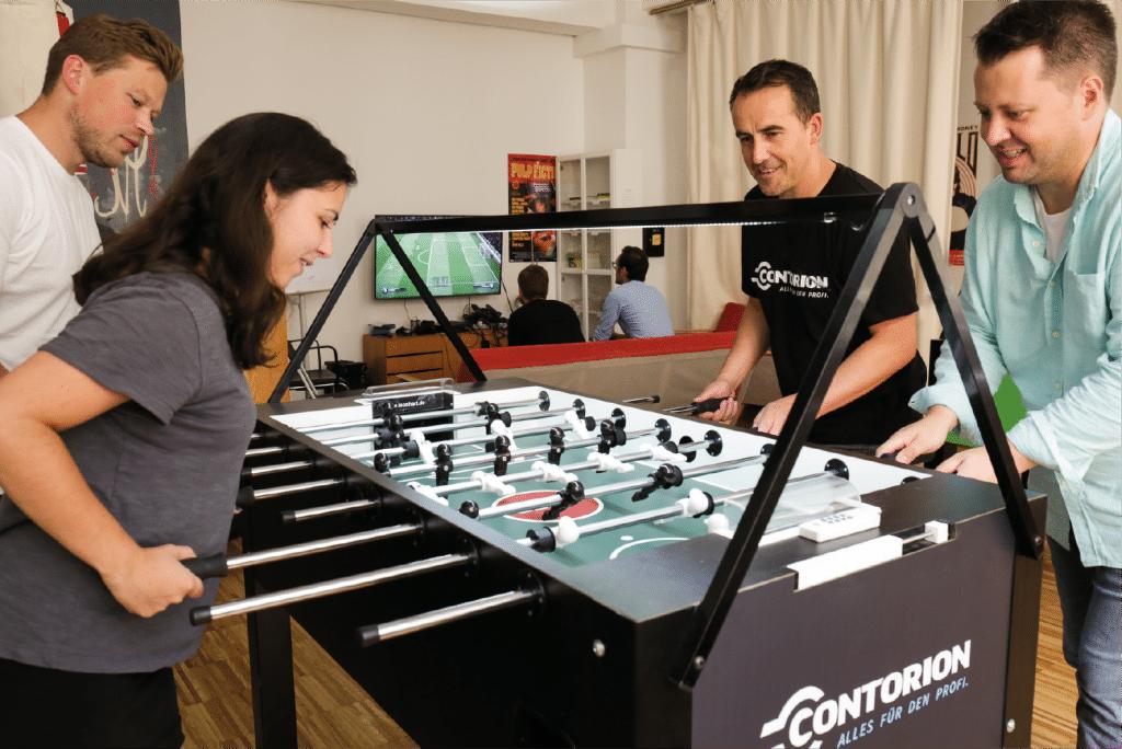 Vier Kollegen von Contorion spielen am Kickertisch im Pausenraum