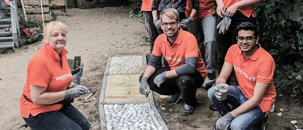 Drei Contorion-Mitarbeiter posieren an einem Barfußpad, den sie gerade gebaut haben. Sie tragen orange Polohemden