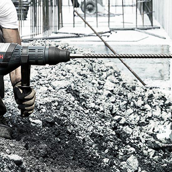 Bauarbeiter befindet sich auf einer Baustelle im Freien und bohrt mit einer Bohrmaschine in eine Betonwand