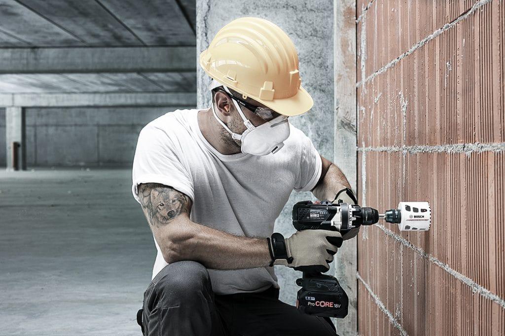 Ein Handwerker mit gelbem Helm sägt mit einer Bosch Carbide Lochsäge in eine Ziegelwand