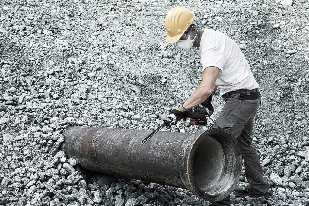 Bauarbeiter auf einer Baustelle draußen mit gelbem Helm sägt ein Abflussrohr
