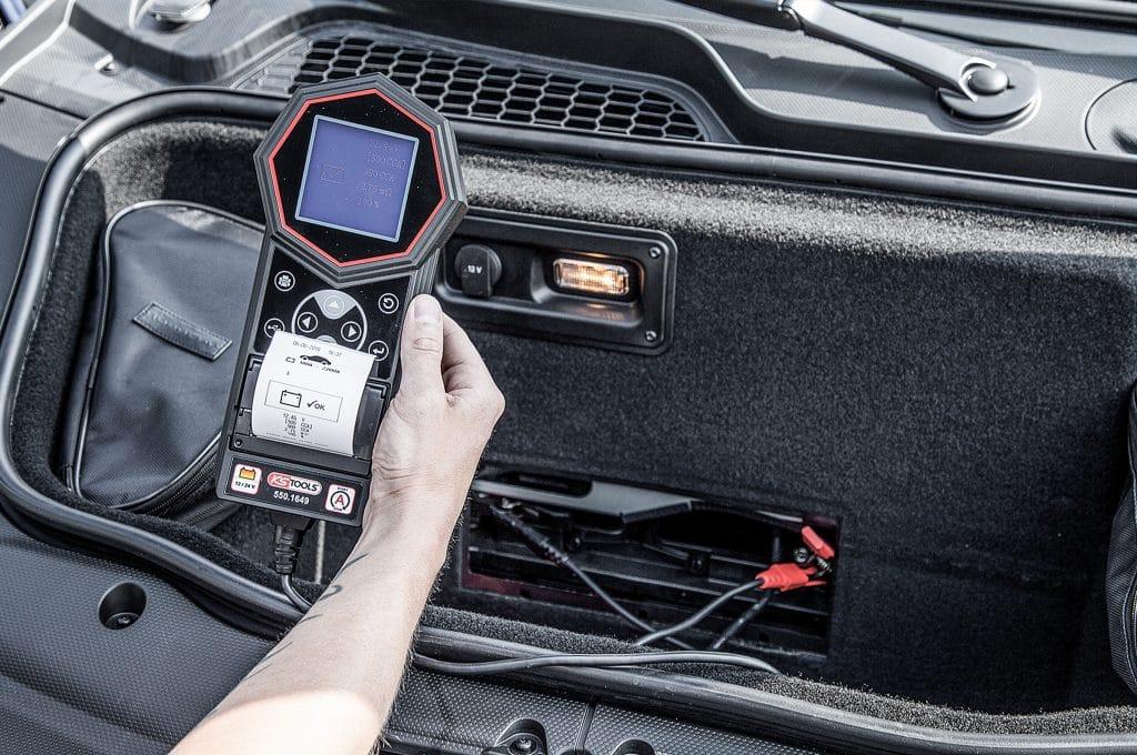 Kfz-Mechaniker testet mit dem KS Tools Batterietester den Stand einer Autobatterie.
