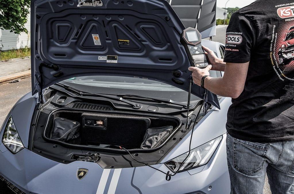 Eine Person mit KS Tools T-Shirt hält den digitalen Batterietester in der Hand und wartet auf die Testergebnisse. Wir sehen die geöffnete Motorhaube eines Porsches