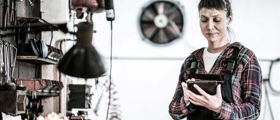 Eine junge Handwerkerin im Holzfällerhemd sitzt in der Werkstatt und bedient ein Tablet. Sie lächelt.