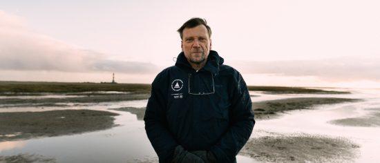 Rainer Schulz, Leiter der Schutzstation Wattenmeer, steht auf dem Watt und schaut frontal in die Kamera