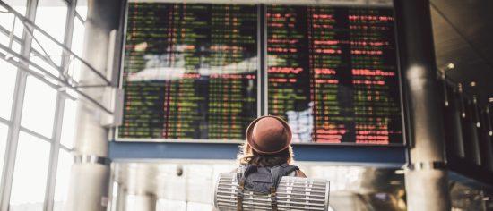 Eine junge Frau mit rotem Hut steht vor der Anzeigetafel an einem Flughafen