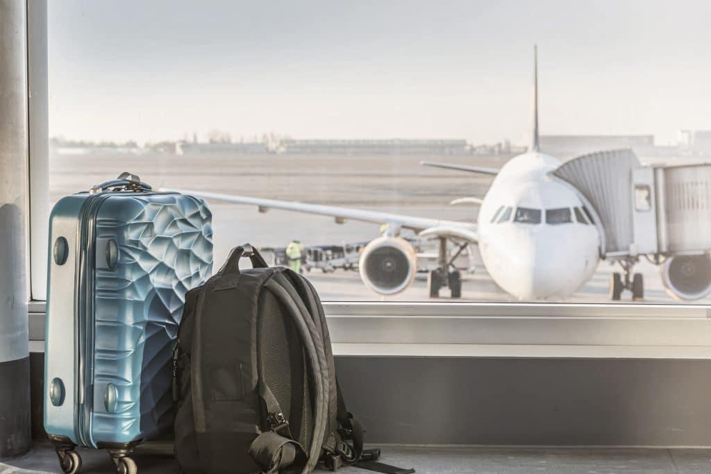 Reisegepäck steht vor einem großen Fenster. Durch das Fenster blicken wir auf ein Flugzeug