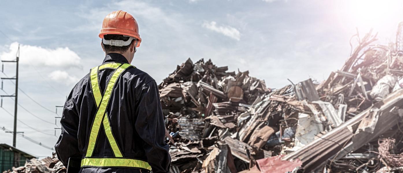 Ein Handwerker mit orangem Helm steht vor einem riesigen Berg Metallschrott