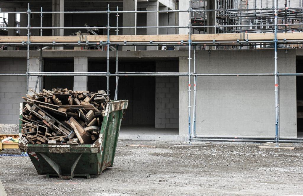 Ein Container gefüllt mit Bauschrott steht vor einem Haus auf einer Baustelle