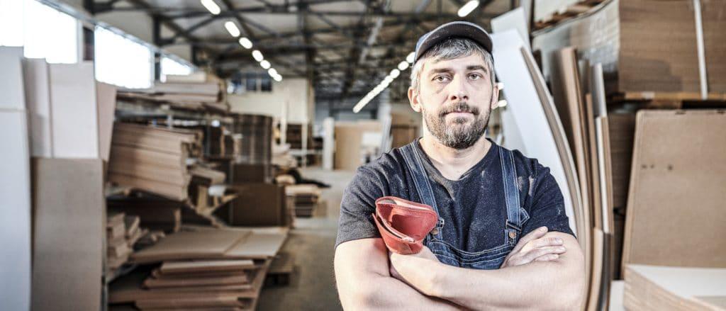 Ein Handwerker im Blaumann steht in der Werkstatt und schaut ernst in die Kamera