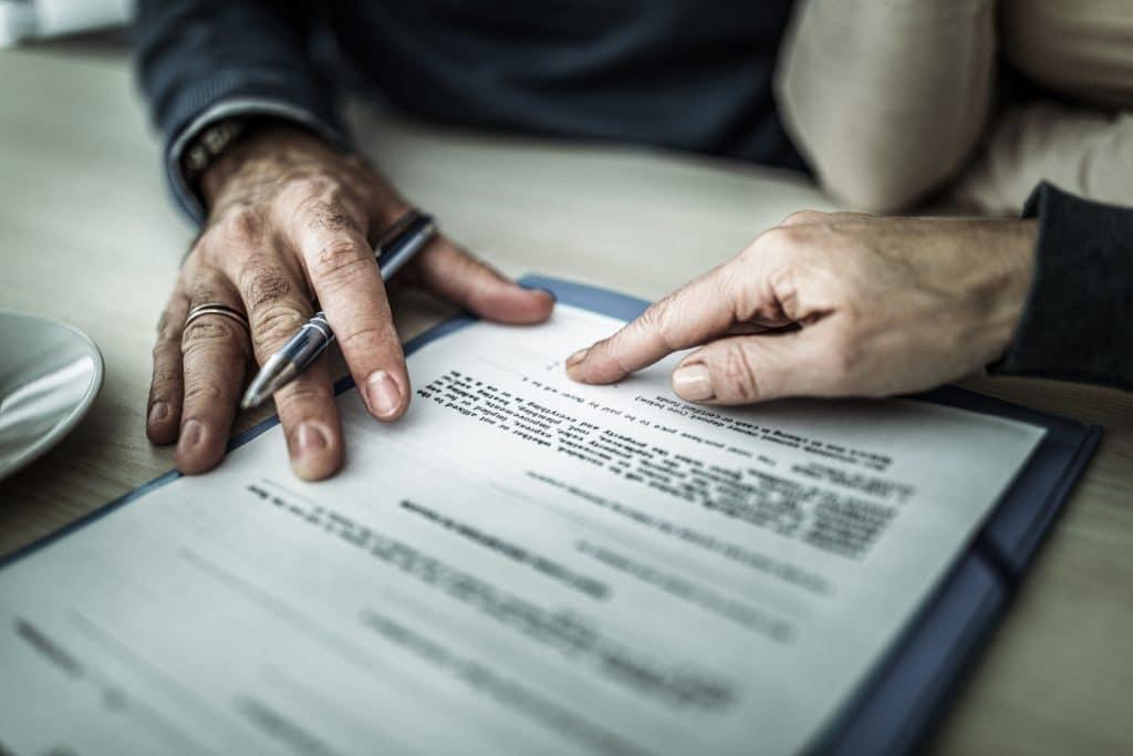 Zwei Personen sind über einen Arbeitsvertrag gebeugt und diskutieren