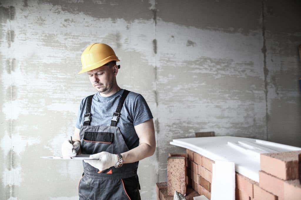 Bauarbeiter mit gelbem Helm unterzeichnet ein Papier auf einem Klemmbrett in seiner Hand