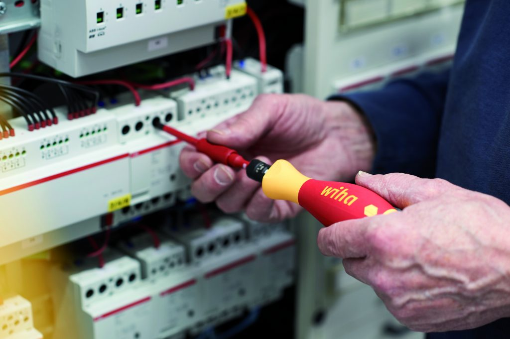 Ein Elektriker verwendet einen Schraubendreher von Wiha, um einen Stromkasten zu reparieren