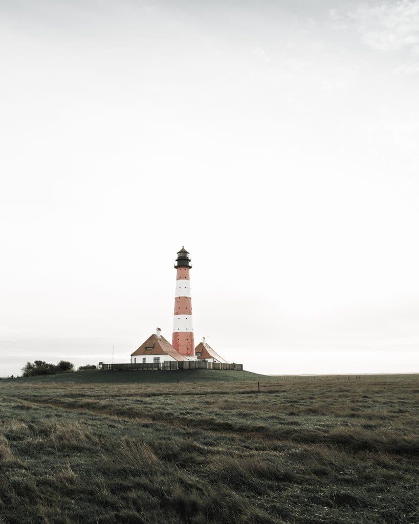 Panorama-Aufnahme des rot-weiß gestreiften Leuchtturms Westerheversand