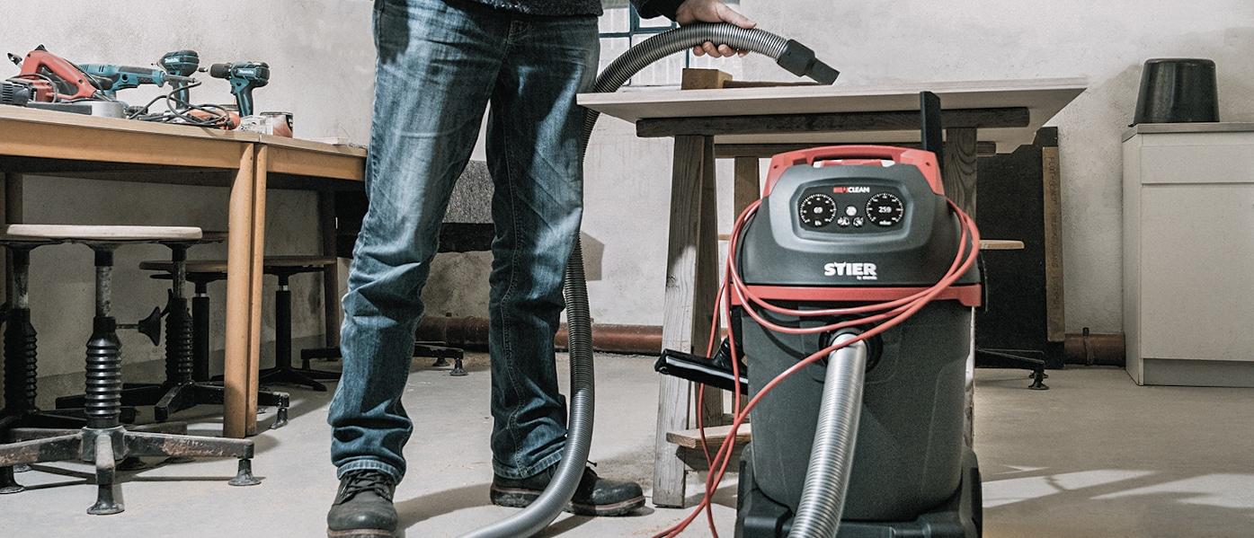 In der Werkstatt saugt jemand mit dem STIER Staubsauger Sägespäne vom Arbeitstisch