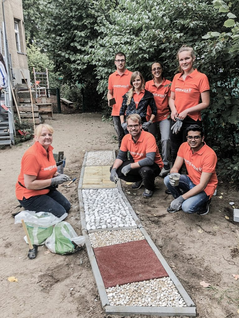 Sechs Contorion-Mitarbeiter in orangen Hemden präsentieren stolz ihr Werk