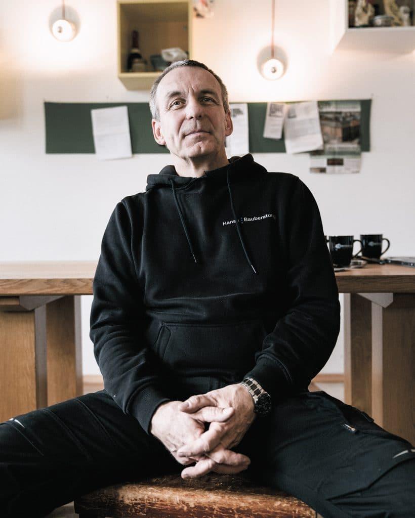Hans von Bülow vom Handwerkerhof Hamburg sitzt in der Küche und schaut frontal in die Kamera