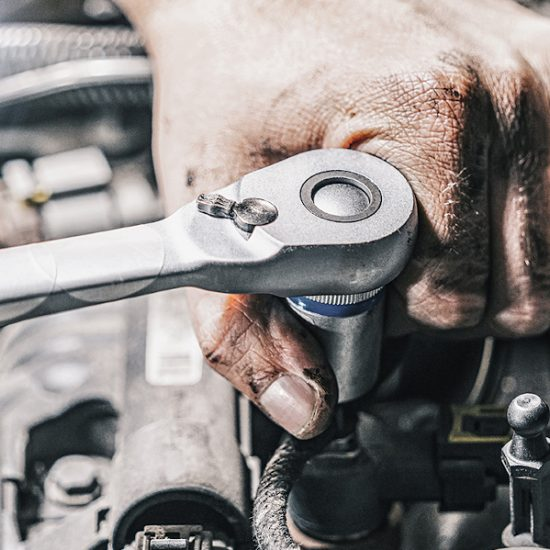 Wir sehen die Hände eines Automechanikers, der gerade einen Drehmomentschlüssel im Motor eines Fahrzeuges anwendet