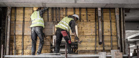 Zwei Bauarbeiter in Warnwesten stehen auf einem Gerüst und arbeiten an einer Betondecke