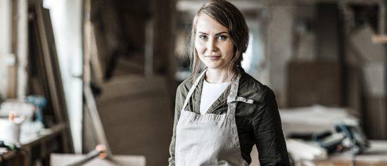 Eine junge Handwerkerin steht in ihrer Werkstatt und schaut freundlich in die Kamera