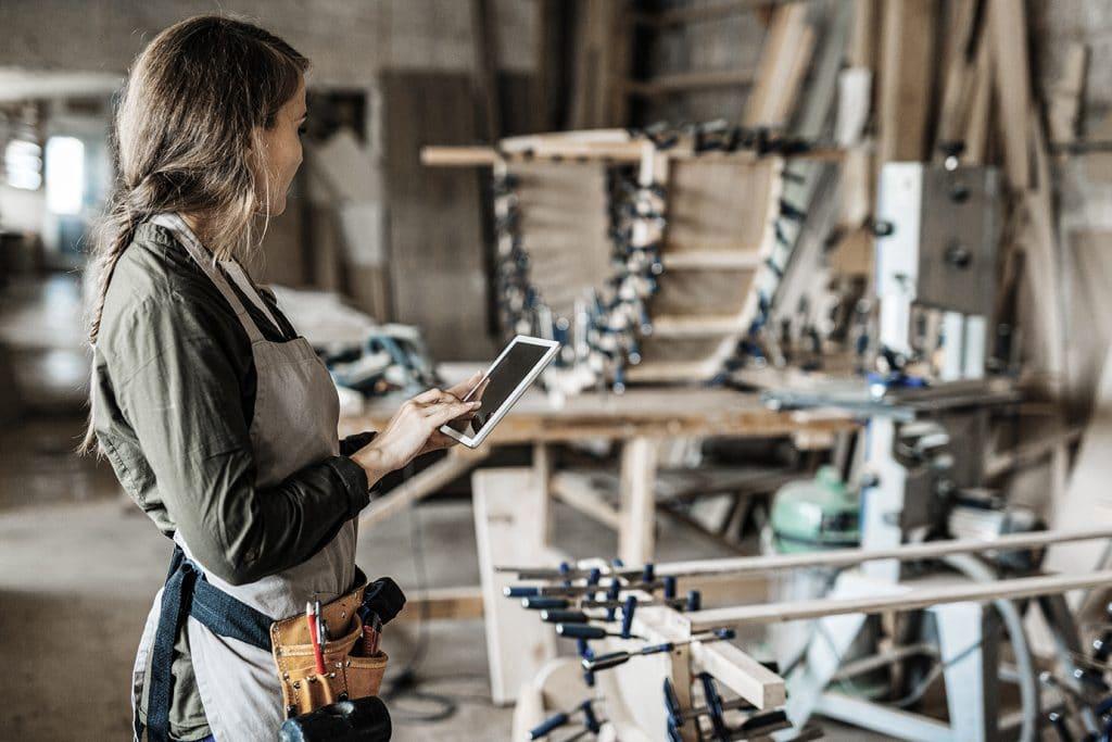 Eine Handwerkerin steht in einer Holzwerkstatt und hat ein Tablet in der Hand