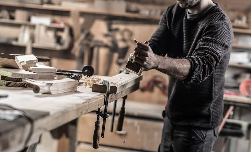 Ein Holzhandwerker arbeitet an der Werkbank in seiner Holzwerkstatt