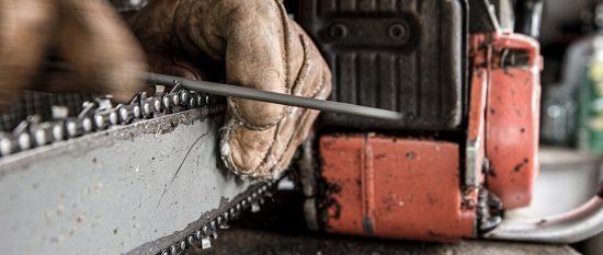 Ein Handwerker schärft die Kette seiner Motorsäge mit einer Feile und trägt Arbeitshandschuhe
