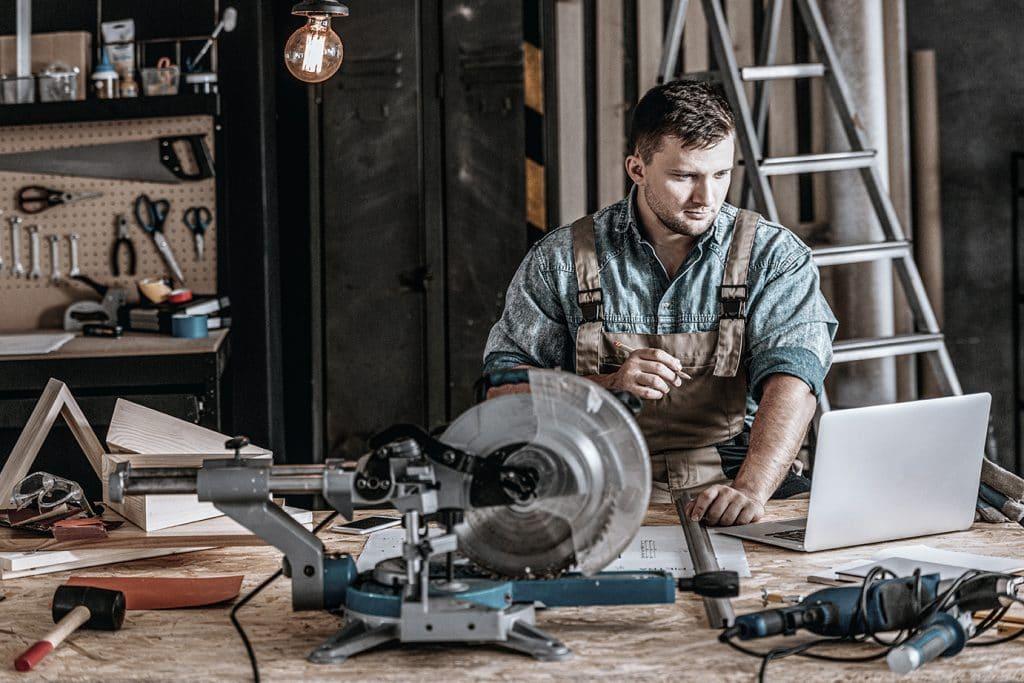 Ein junger Tischler sitzt in einer Holzwerkstatt und plant am Laptop sein nächstes Projekt
