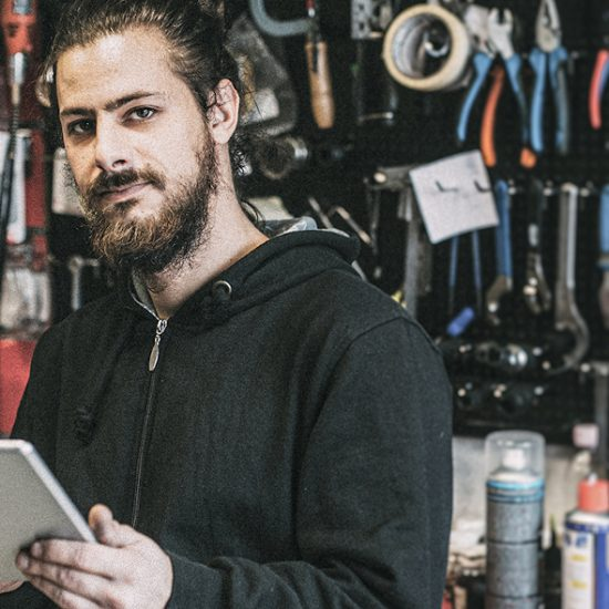 Ein junger Fahrrad-Mechaniker steht in seiner Werkstatt und schaut frontal in die Kamera, in seiner Hand hält er ein Tablet