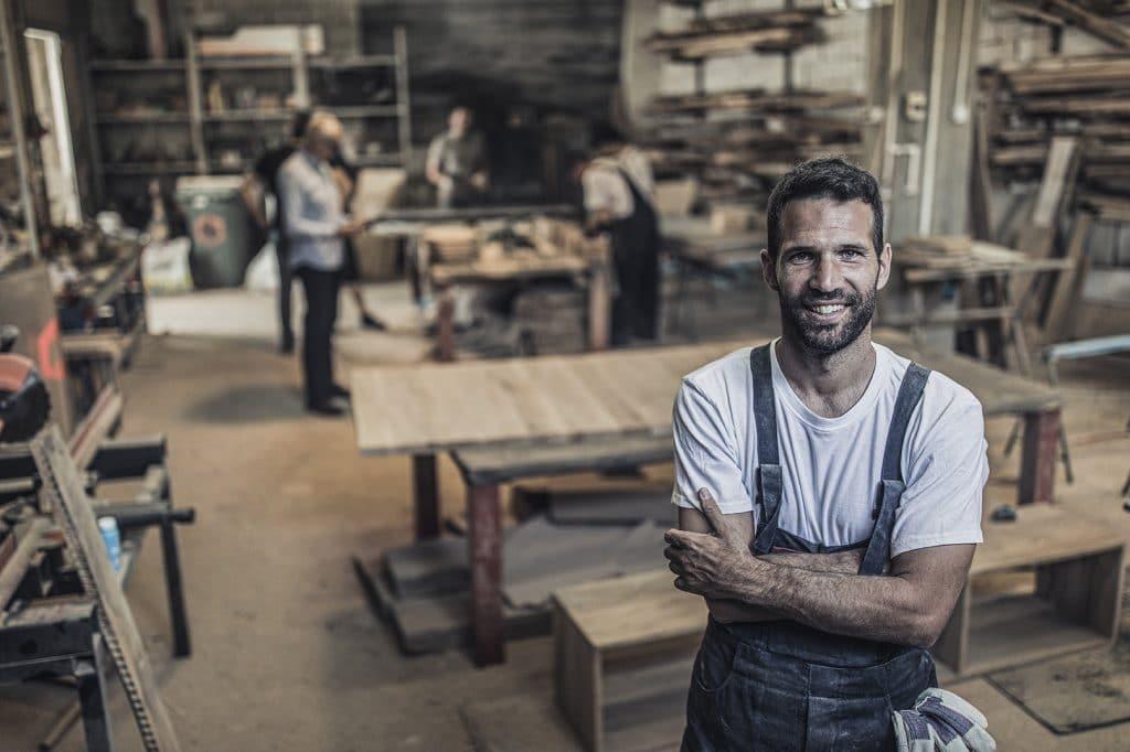 Ein glücklicher junger Handwerker steht in seiner Werkstatt und schaut frontal in die Kamera