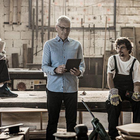 Ein älterer Herr im Hemd und zwei junge Handwerker sitzen und stehen in einer Werkstatt und planen ein neues Projekt