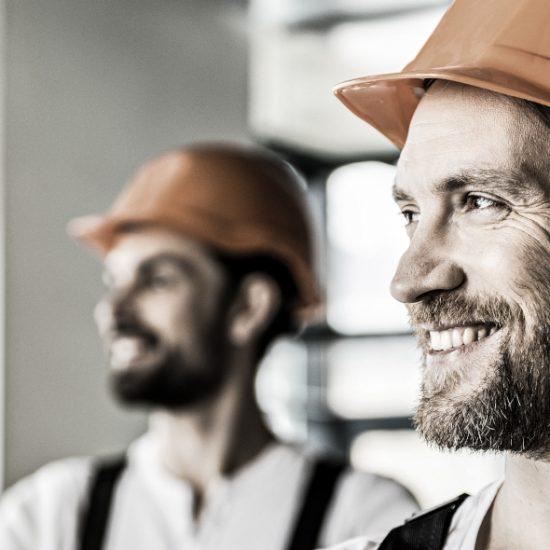 Zwei junge Handwerker mit orangenen Helmen schauen zuversichtlich und glücklich nach links