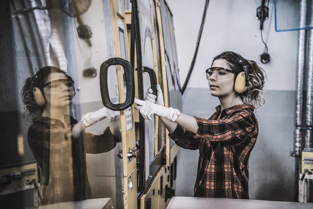 Junge Auszubildende im Handwerk bedient eine Produktionsmaschine
