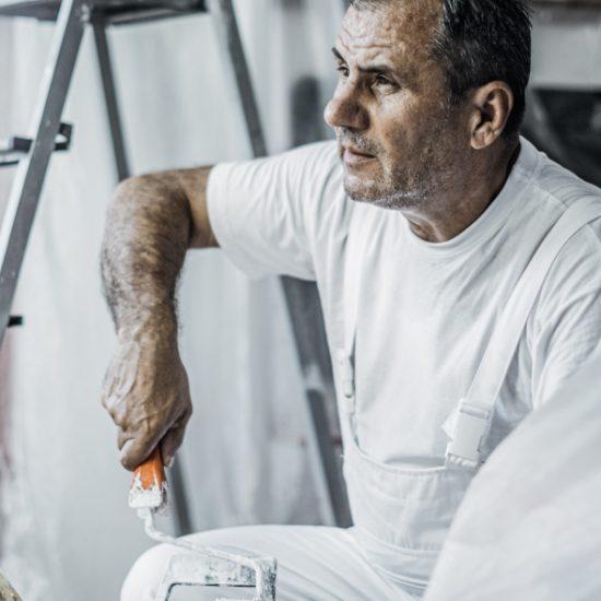 handwerker in weißer arbeitskleidung hält farbrolle in der hand