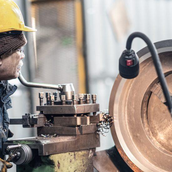 senior handwerker bearbeitet in der industriellen fertigung ein werkstück