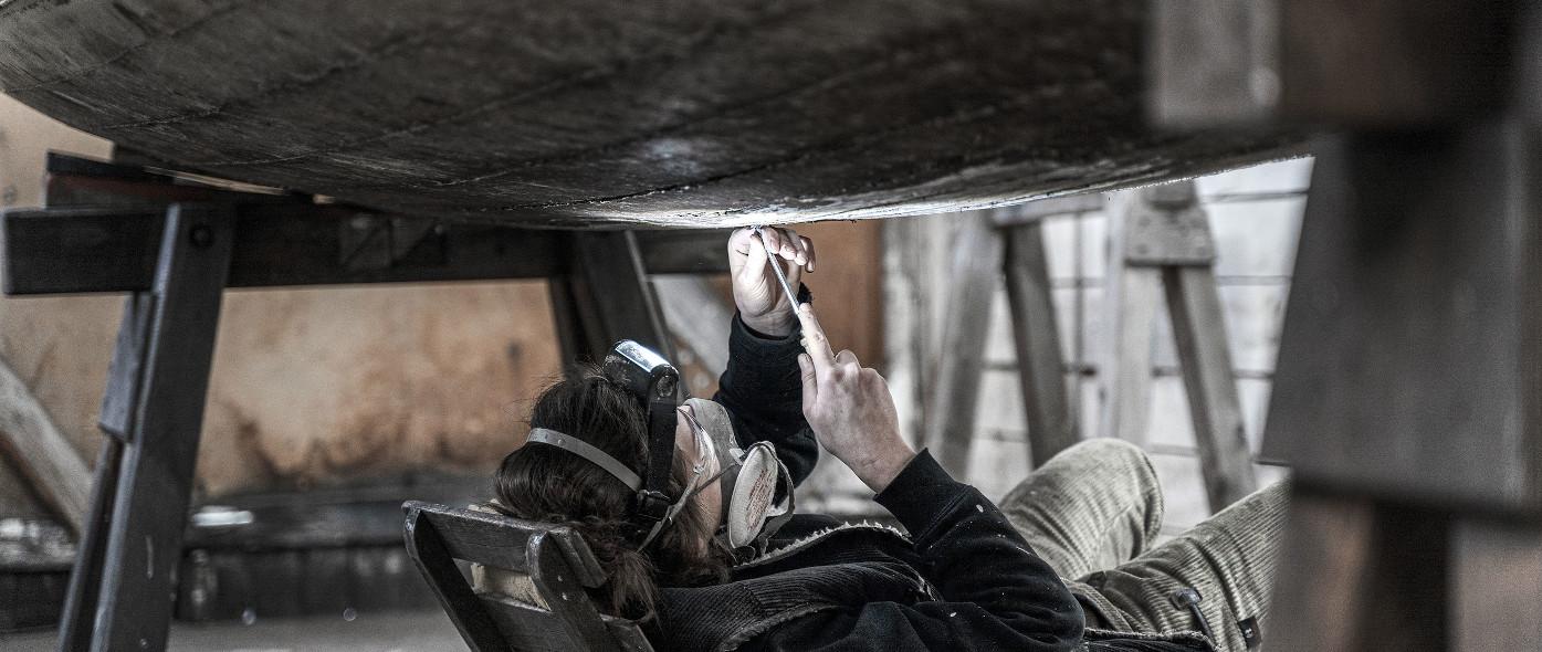 Bootsbauerin liegt unter einem Holzboot und repariert es