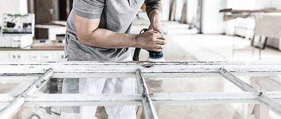 bewegung-tut-gut-festool-schleifer-handwerker beim shcleifen eines fensterrahmens