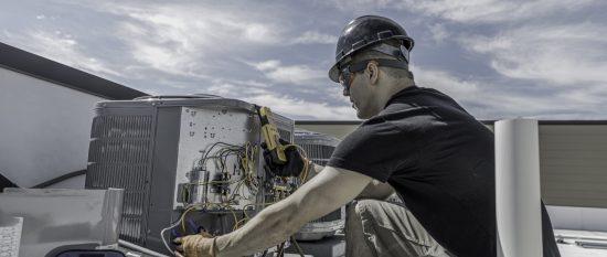 Hvac-Techniker bei der Arbeit an einer Kondensationsanlage auf dem Dach