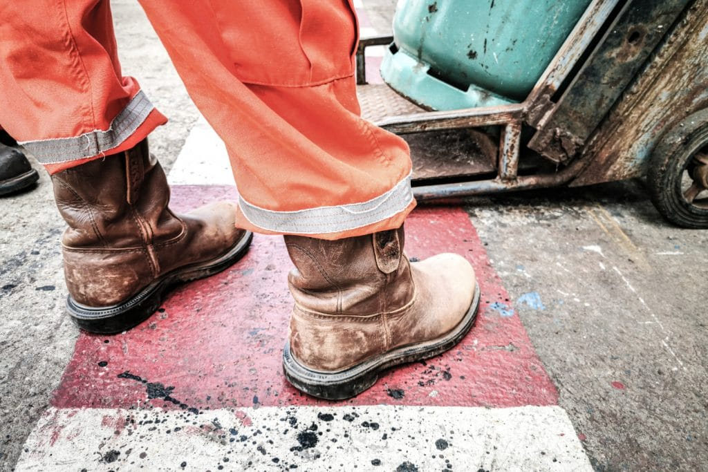 Der Vorgesetzte steht für die Durchführung der Geräteinspektion in der Industriewerkstatt. Fokus auf Sicherheitsschuh.