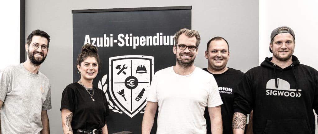 azubi-stipendium-shortlist-die jury steht vor roll-up und lachen in die kamera