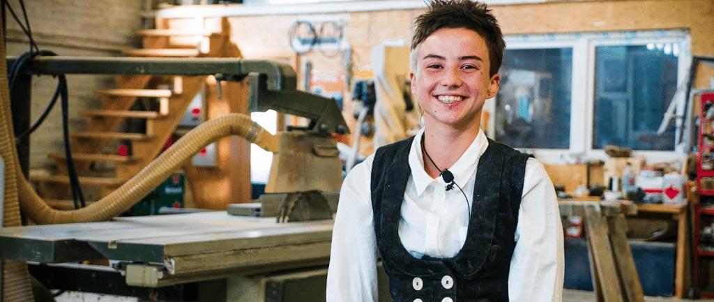 Die Gewinnerin des Azubi-Stipendiums Maja sitzt fröhlich und in Zimmermannskleidung in einer Holzwerkstatt
